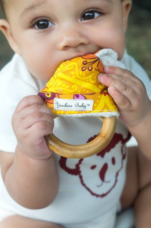 Baby is wearing a Koala Face Organic Cotton Onesie and using a Natural and Organic Teether.