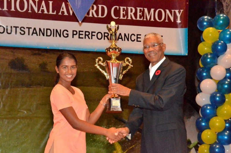 President David Granger presenting an award to Victoria Najab from the Saraswati Vidya Niketan School for the most outstanding candidate at the CSEC level in business education.