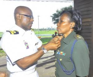 Commodore Gary Best decorates Col. Algernon with her new Badge of Rank.