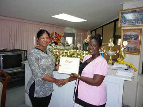 Michelle Kandasammy presents  BPP inductee certificates to Queen's College Headmistress, Mrs. Hollingsworth - in Guyana.