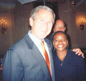 Marian Burnett posing with President Bush at the White House in 2003