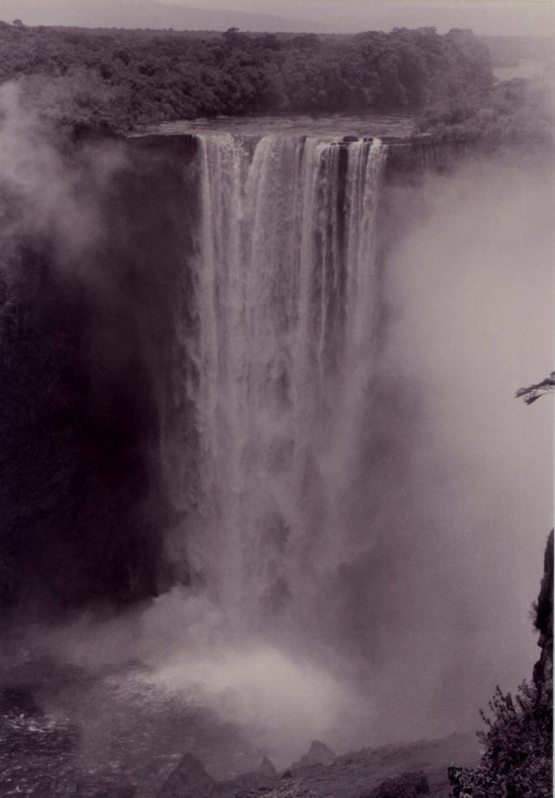 A misty veil attends the thunderous curtain of water. Kaiteur Falls, Guyana